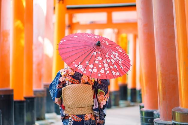 Девушка-гейша в японском кимоно среди красных деревянных ворот тори в храме фусими инари в киото