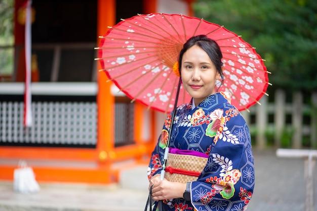 Девушка-гейша в японском кимоно среди красных деревянных ворот тори в храме фусими инари