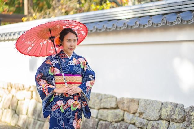 Geishas girl wearing japanese kimono among red wooden tori gate