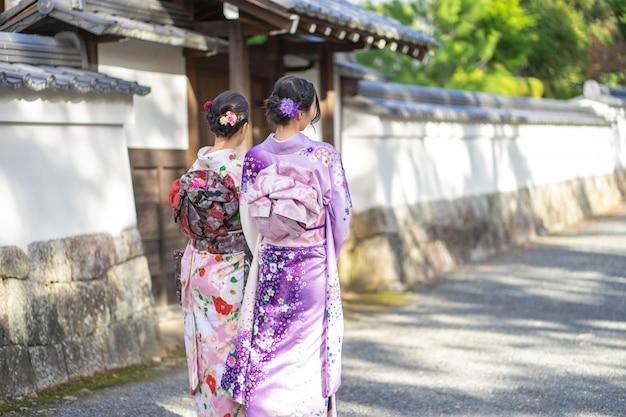 Geishas girl wearing japanese kimono among red wooden