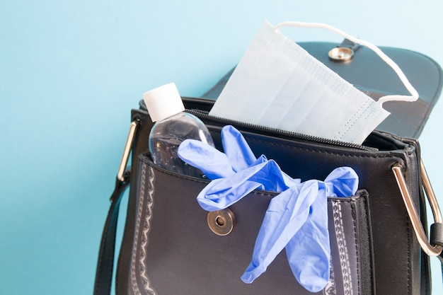 Дезинфицирующее средство на основе спирта, маска для лица и синие резиновые одноразовые перчатки в сумочке на синей поверхности