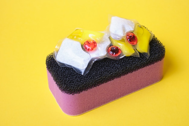 Gel capsules for dishwashers and sponges on a yellow background