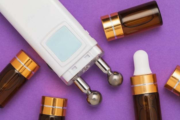 Гель в ампулах и прибор для микротоковой стимуляции лицевых мышц на фиолетовом
