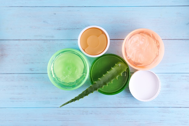 Gel serum of snail collagen and fresh aloe vera gel in jar on blue wooden background