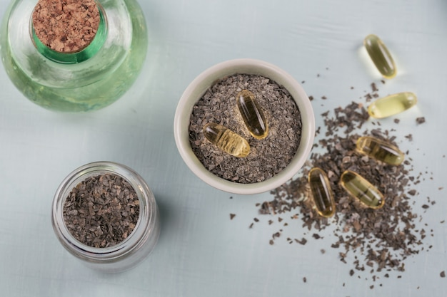 Желатиновые капсулы с маслом омега водорослей и водорослями на голубом