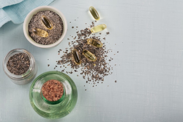 Желатиновые капсулы с маслом омега водорослей и водорослями на светло-сером цвете. пищевые добавки. вид сверху с пространством для текста