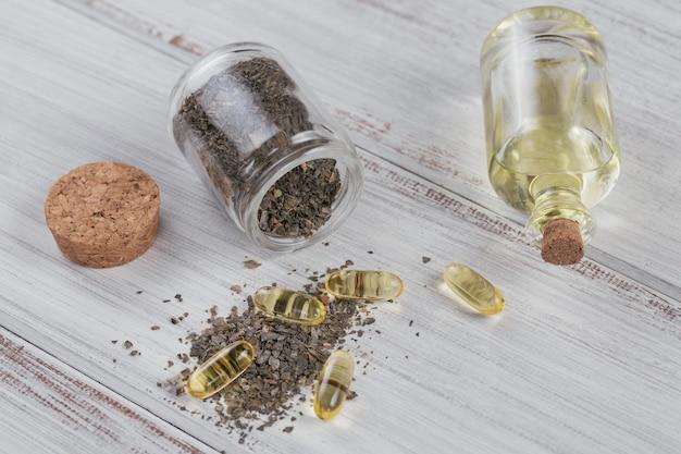 Желатиновые капсулы с маслом омега водорослей и водорослями на белом деревянном фоне. пищевые добавки.