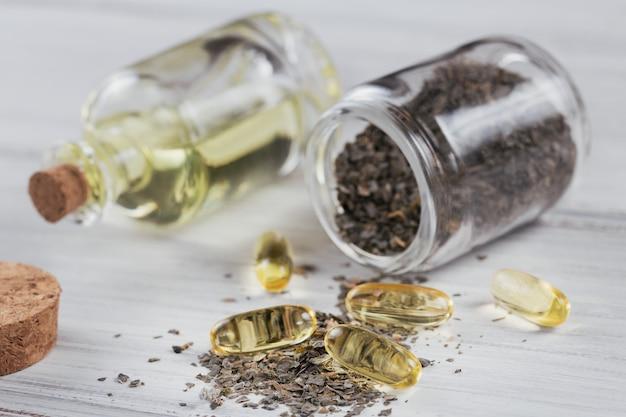 Желатиновые капсулы с маслом омега водорослей и водорослями на белой деревянной поверхности