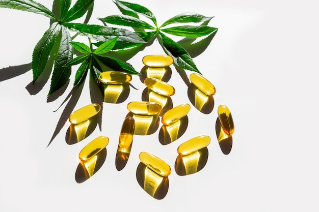 Gelatin softgels capsules of omega-3 fats decorated with green leaves on white table. eicosapentaenoic acid and fish oil. organic natural supplements concept