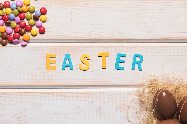 Gem candies and whole chocolate easter eggs with easter word over the wooden desk