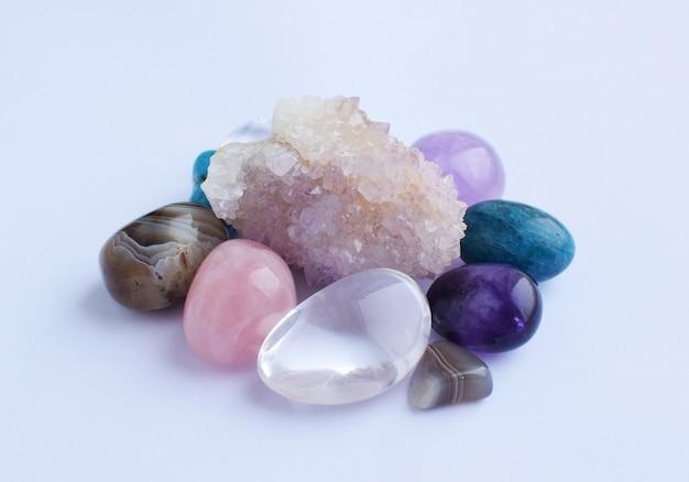 Драгоценные камни ярко окрашены, необработанные и обработанные. кактус аметист, розовый кварц, агат, апатит, авантюрин на белой стене.