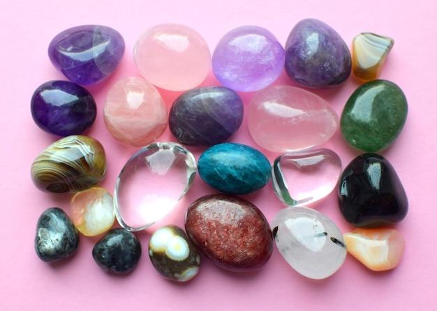 다양한 색상의 보석. 자수정, 장미 석영, 마노, 인회석, 어벤츄린, 감람석, 청록색, 아쿠아마린 및 분홍색 배경의 암석 수정