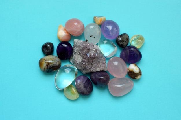 다양한 색상의 보석. 자수정, 장미 석영, 마노, 인회석, 어벤츄린, 감람석, 청록색, 아쿠아마린, 파란색 배경의 암석