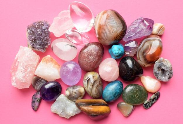 다양한 색상의 보석. 자수정, 장미 석영, 마노, 인회석, 어벤츄린, 감람석, 청록색, 아쿠아마린, 분홍색 배경의 암석