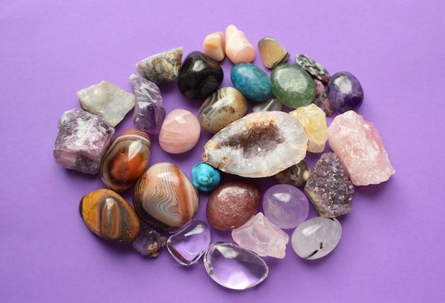 다양한 색상의 보석. 자수정, 장미 석영, 마노, 인회석, 어벤츄린, 감람석, 청록색, 아쿠아마린, 보라색 배경의 암석