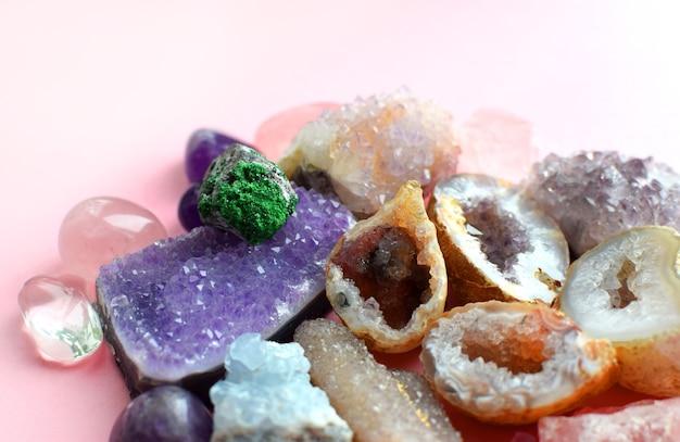 さまざまな色の宝石。ジオードアメジスト、ローズクォーツ、瑪瑙、アパタイト、アベンチュリン、オリビン、ターコイズ、アクアマリン、ロッククリスタルはピンクの背景にあります