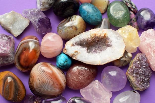 다양한 색상의 보석. 지오드 자수정, 장미 석영, 마노, 인회석, 어벤츄린, 감람석, 청록색, 아쿠아마린, 보라색 배경의 암석