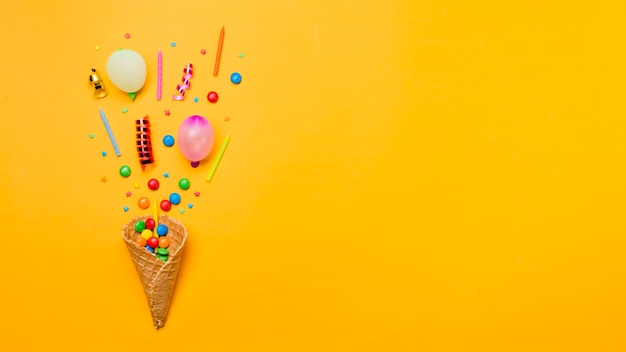 Gems; sprinkles; streamers; candles and balloon over the waffle cone on yellow background