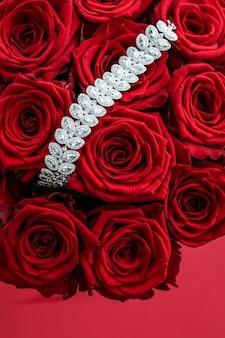 ジェムストーンジュエリーファッションと豪華なショッピングコンセプトの豪華なダイヤモンドブレスレットと赤いバラの花束