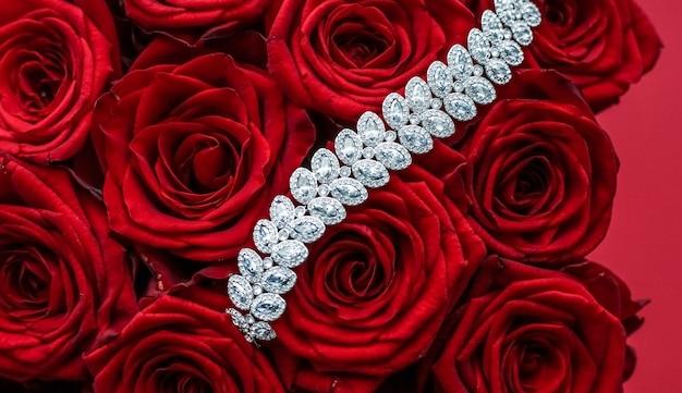 ジェムストーンジュエリーのウェディングファッションと豪華なショッピングコンセプトの豪華なダイヤモンドブレスレットと赤いバラの花束ジュエリーはバレンタインデーとロマンチックな休日のプレゼントにギフトを愛します