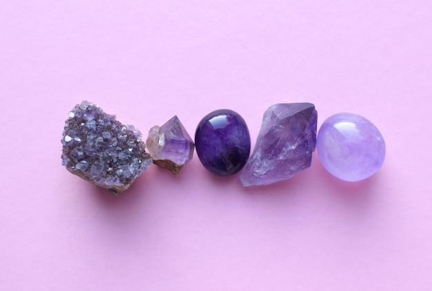 분홍색 배경에 보석 광물입니다. 자수정과 자수정 크리스탈의 둥근 텀블링 광물.