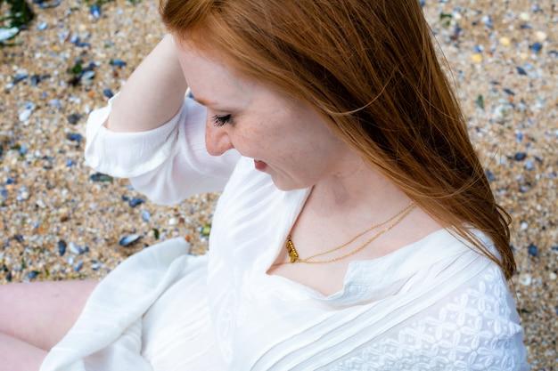 クローズアップ手若い女性ビーチ海赤髪太陽北砂白いドレススヘフェニンゲンgen haag