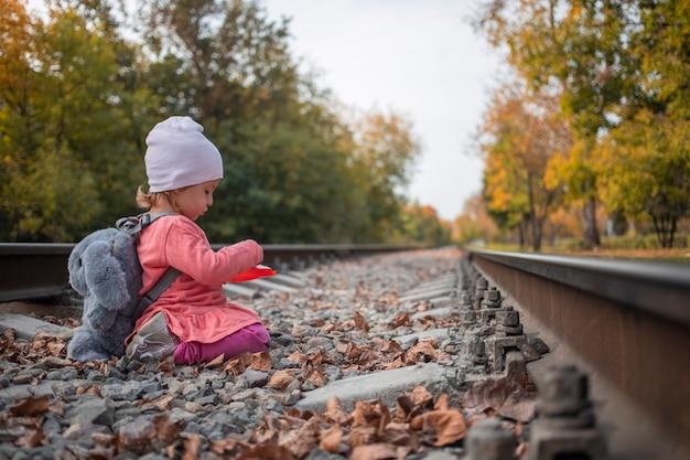 子供の性差。かわいい女の子が線路で遊ぶ。