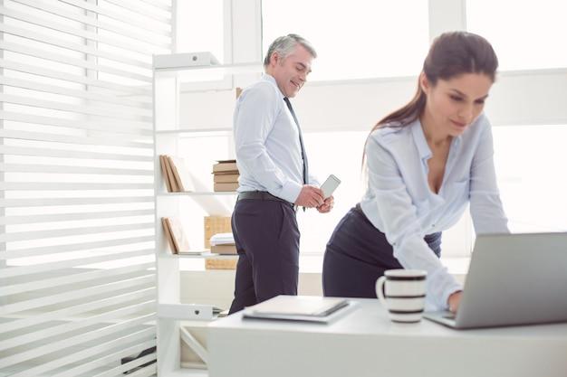 Дискриминация по полу. неприятный веселый взрослый мужчина стоит за своей коллегой и фотографирует ее, используя свой смартфон