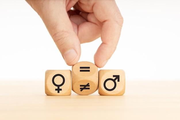 Концепция гендерного равенства. рука поворачивает деревянный брусок и меняет знак неравенства на знак равенства между символами мужчин и женщин.