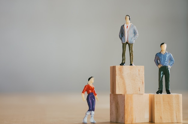 Gender equality concept, miniature female figurine stand lower than male figurines