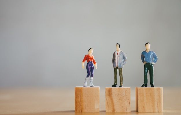 Gender equality concept, miniature female figurine stand same level as male figurines