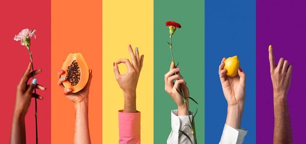 ジェンダー流動的な人々は虹の背景を手渡します