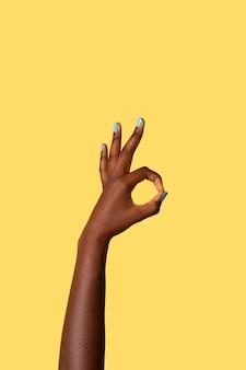 Mano di persona fluida di genere isolata su giallo
