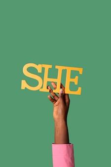Гендерный человек, держащий бумажное местоимение женского рода