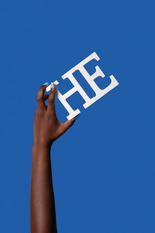 Persona fluida di genere che tiene un pronome isolato su blu