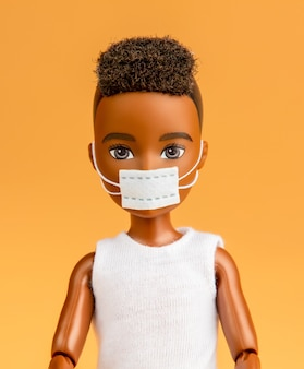 Gender-neutral africanian doll in face mask on yellow background