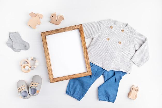 Gender neutral baby garment and accessories and empty frame mockup. organic cotton clothes, newborn fashion, branding, small business idea. flat lay, top view