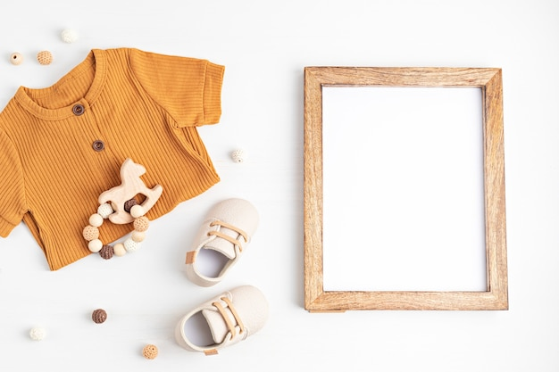 Gender neutral baby garment, accessories and empty frame. organic cotton clothes, newborn fashion, branding, small business idea. flat lay, top view