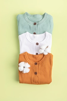 Детская одежда нейтрального пола. одежда из органического хлопка, мода для новорожденных, брендинг, идея для малого бизнеса. плоская планировка, вид сверху