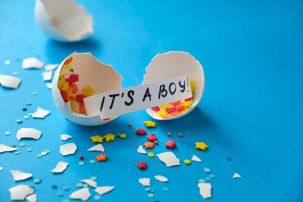 性別披露パーティー。男の子か女の子。色付きの紙吹雪とメッセージが付いた壊れた卵の殻青い背景の男の子です。子供の性別がわかったときのお祝いのコンセプト