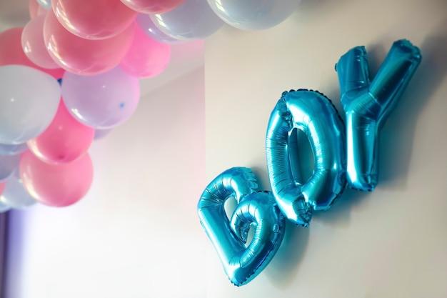 성별은 소년 또는 소녀의 흰색 벽 정의에 있는 거실에서 파티 파란색과 분홍색 풍선을 나타냅니다.
