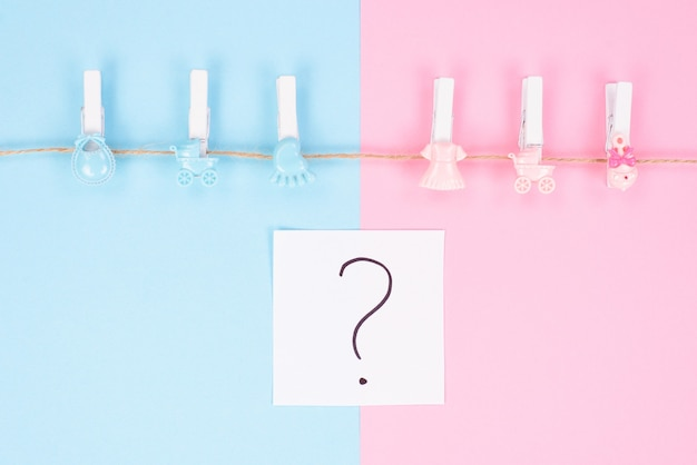 Gender reveal party invitation concept. background photography of small pegs with carriage toys isolated on divided into two parts background question mark in center