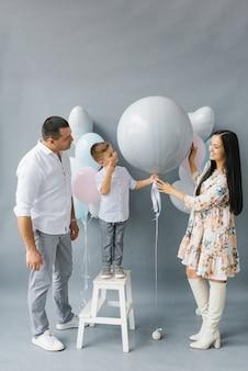 性別披露パーティー。赤ちゃんを持つスタイリッシュな美しい家族は、家族の胎児の性別を見つけるために風船をポップします