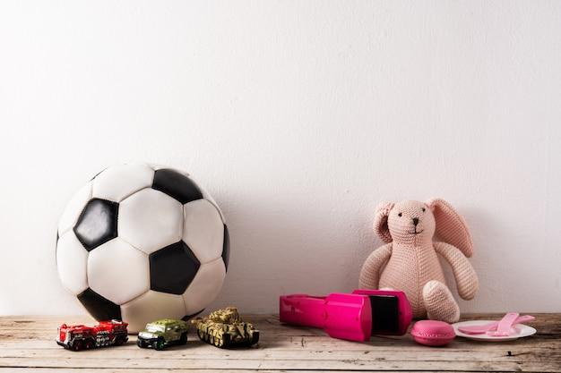 Гендерные стереотипные игрушки на деревянном столе и белом
