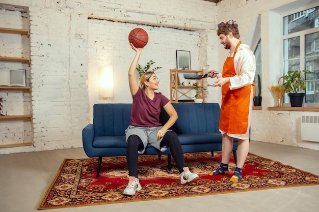 성별 고정 관념. 아내와 남편은 사회적 의미에서 성별에 따라 비정상적인 일을 합니다. 여자가 거실에서 공을 가지고 농구 훈련을 하는 동안 남자가 저녁 식사를 요리합니다.