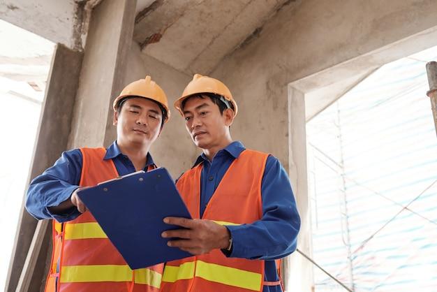 ゼネコンが現場で会う際に下請け業者の工事進捗報告書を確認する