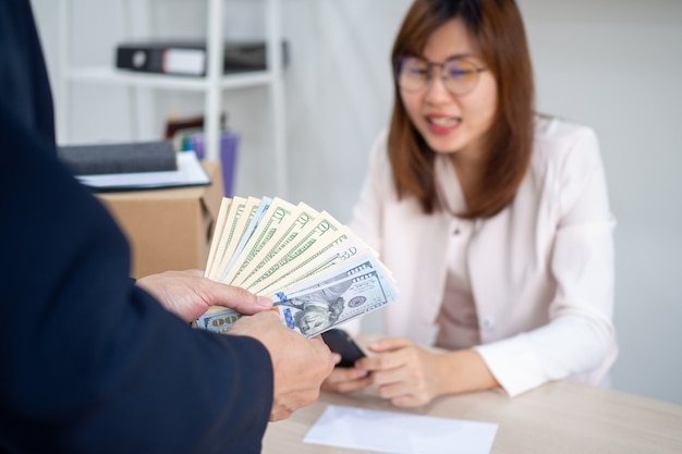 ゼネラルマネージャーがプレミアムまたはボーナスの現金の封筒を女性の役人に提示します。上司はキャリアアップで幸せな従業員を祝福し、良い仕事に感謝し、経済的報酬を与える