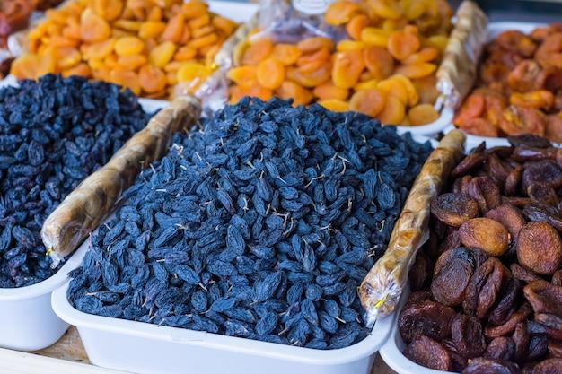 Общий план прилавка магазина с продажей различных сухофруктов. калорийное питание из сухофруктов. фрукты фиников, сушеные персики, инжир, абрикосы, изюм, курага