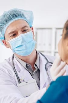 Врач общей практики осматривает железы пациента