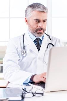 일반 개업의. 작업장에 앉아 노트북 작업을 하는 성숙한 회색 머리 의사